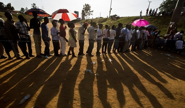 """Ugandans continue to queue to cast their votes at sunset in the capital Kampala, Uganda Thursday, Feb. 18, 2016. Amid tardy delivery of voting materials, Ugandans tried to cast ballots Thursday in presidential and parliamentary elections, while a top international election observer called the delays """"worrying"""" and the main opposition party said they were deliberate. (AP Photo/Ben Curtis)"""